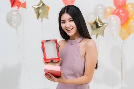Attractive young asian woman happy and surprise while open gift box at party, portrait shot white background with festive balloon.