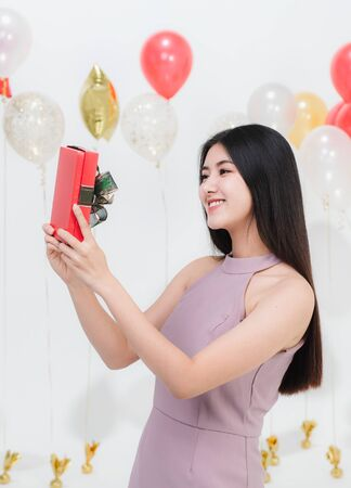 Beautiful young asian woman happy appreciate with gift box at party, portrait shot white background with festive balloons.