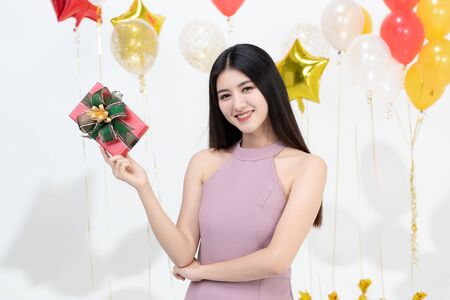 Beautiful young asian woman big friendly smile posig with gift box happy at fun party, portrait shot white background with colorful balloons. Imagens