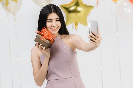 Attractive young asian woman in pink dress, selfie with her gift box at fun party, white background with festive colorful balloons.