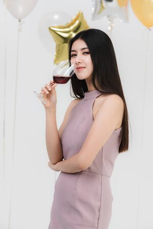 Attractive young asian woman in pink dress, drinking wine and happy at fun party, portrait on white background with colorful festive balloons. Standard-Bild