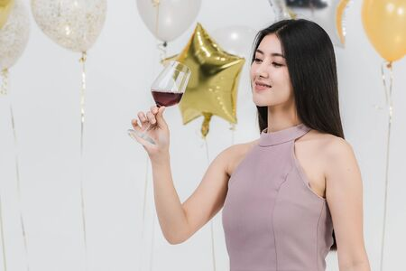 Attractive young asian woman in pink dress, holding her drink and happy at fun party, portrait on white background with colorful festive balloons.