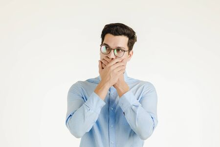 Young hipster office man covering his mout by hands as keep secret or silence sign, portrait shot isolated on white background.