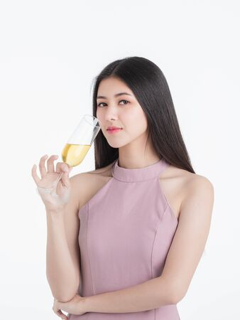Beautiful young asian woman in pink dress, confident introvert posing with champagne glass, portrait short isolated on white background.