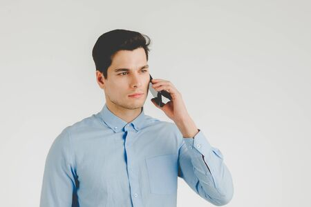 Young hipster man confident and serious talking on phone for business work,  portrait isolated on white background.