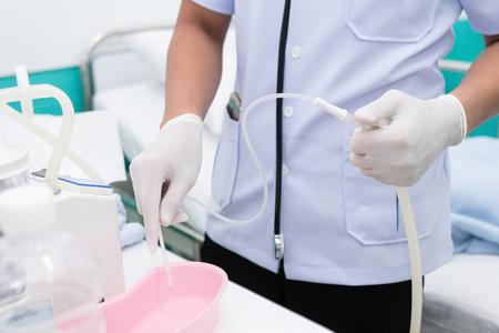 Nurse use Suction Machine, prepare to suction patient's mucus.