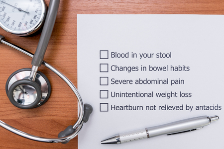 colorectal: In the doctors Office There is a form that the doctor made to diagnose the disease that indicate Colon Cancer in a patient. Diagnosis form placed on the doctors desk. Stock Photo