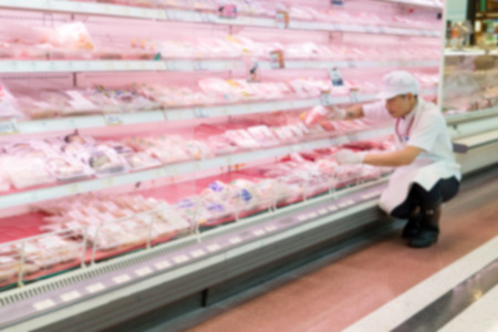 Blurry Background of Butcher sort area of trim meat and placed it on the meat of shelves to sell in the supermarket. Stock Photo