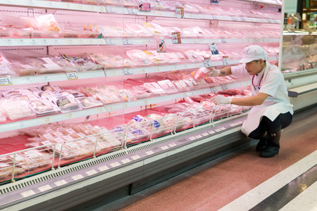 Bangkok, Thailand - August 13, 2017: Butcher sort area of trim meat and placed it on the meat of shelves to sell in the supermarket.
