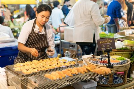 Mega Bangna Shopping Center, Bangkok, Thailand - August 5, 2017: Thai female candy vendor making fresh Thai dessert, its name is Khanom Buang (Thai Crispy Pancake).
