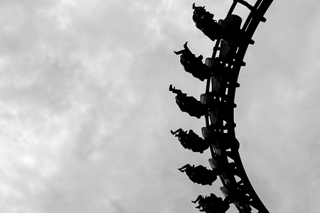 Black and White of People ride roller coaster, legs swinging back and forth as gravity. Stock Photo