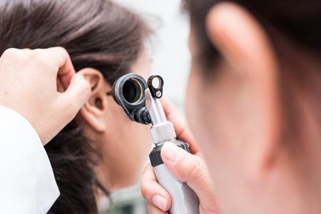 Doktor untersuchte das Ohr des Patienten mit Otoskop. Patienten scheinen Probleme mit dem Gehör zu haben.