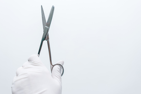 Gloved hand sterilization Expertly holding scissors on white background. Stock fotó