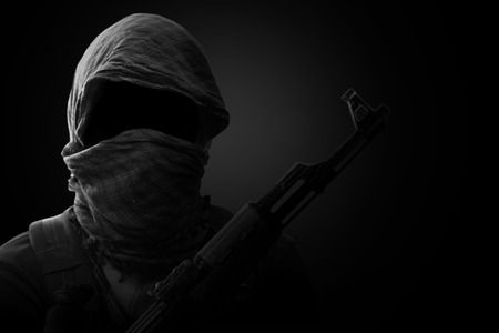 Blurry Background of Terrorist carry weapon hidden in darkness. terrorism concept. on black background with dim light. Black and White. Stock fotó