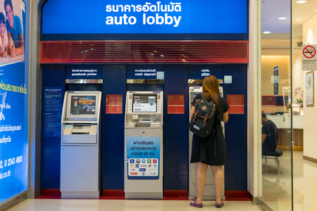 Mega Bangna Shopping Center, Bangkok, Thailand - October 7, 2017: Woman standing cash at bank automatic teller machines. Automatic cash machines or ATMs are very popular nowadays. It is easy to use and comfortable to lifestyle. Sajtókép