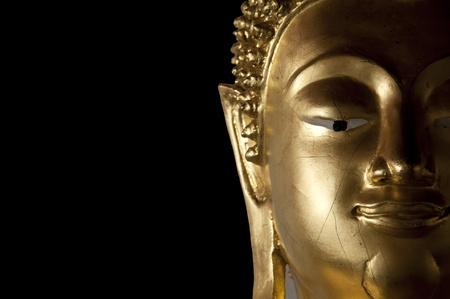 Face of Buddha statue isolated on black background