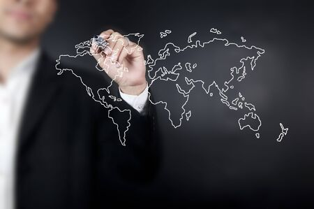 Hand with pen drawing a world map in whiteboard Stock Photo