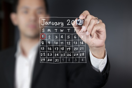 Male hand drawing a calendar photo