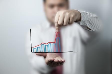 Businessman keeping up a graph