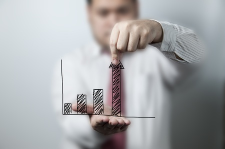 Businessman pulling up a graph Stock Photo