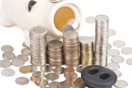 Many money coins stacked up and piggy bank isolated on a white background photo