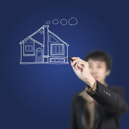 Businessman drawing a home on whiteboard photo