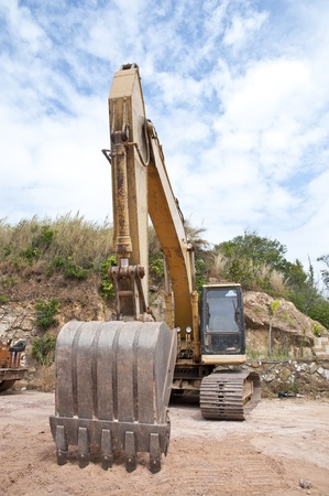 bulldoze: Excavator standing in sandpit with raised bucket over cloudscape sky Stock Photo