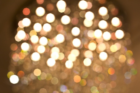 Defocused gold bokeh background with yellow, orange, green and white lights photo