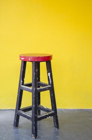 silla de madera: Silla de madera roja delante de la pared amarilla Foto de archivo