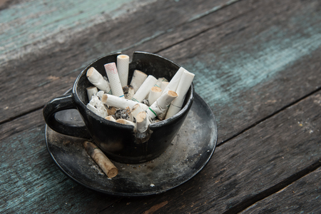 ashy: Ashtray and Cigarettes Close-up on Wooden Background