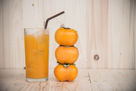 tacky: Orange juice and persimmon on wooden background Stock Photo