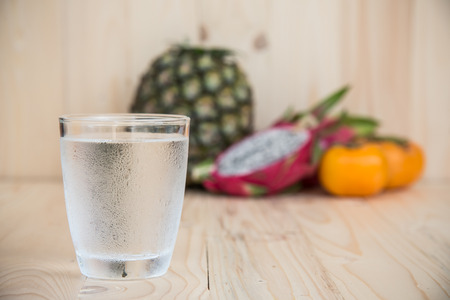 exotic fruits: Drinking water and persimmon, dragon fruit, pineapple on wooden background