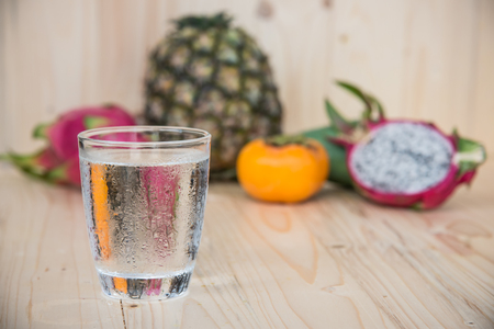 Drinking water and persimmon, dragon fruit, pineapple, mango on wooden background
