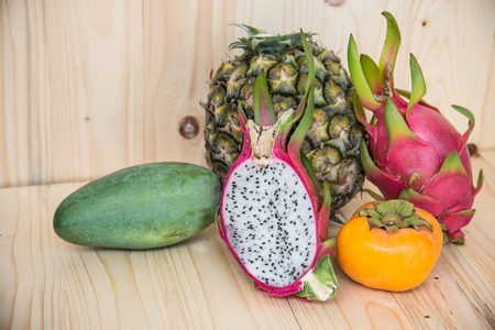 tacky: Persimmon, dragon fruit, pineapple, mango on wooden background