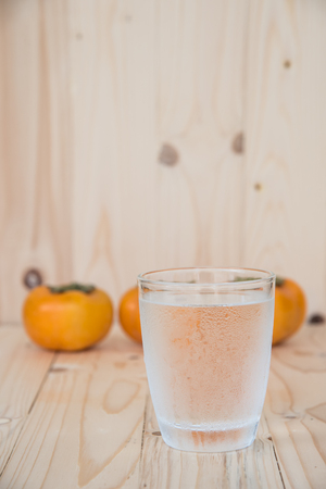 tacky: Drinking water and persimmon on wooden background Stock Photo