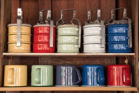 tiffin: Colorful zinc cup and tiffin on wooden shelves Stock Photo