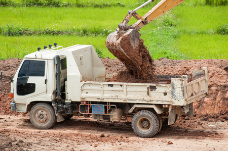 loads: track hoe loads a truck with dirt at a new commercial construction development project
