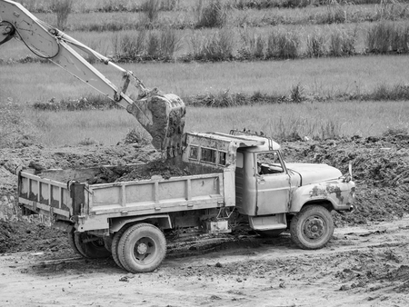 resourcefulness: track hoe loads a truck with dirt at a new commercial construction development project
