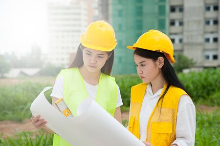 Two womens engineers with blueprint working in a construction site