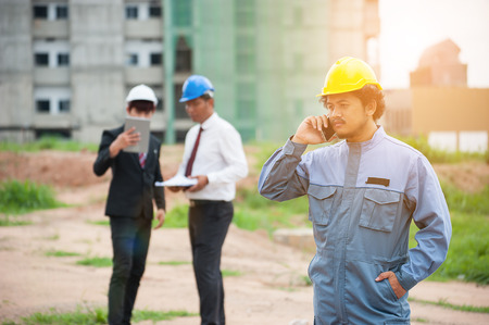 Portrait of young engineer using smartphone in building construction site