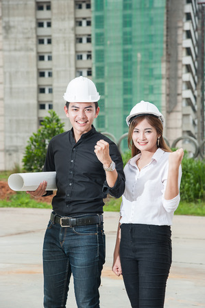 Portrait of beautiful young women and men engineer  wear a white safety helmet smiling on building construction site