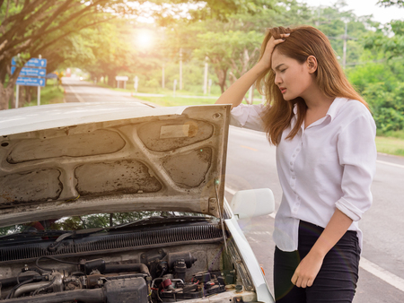 Young woman looking at broken down car on street
