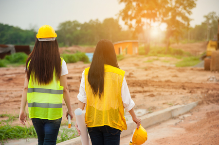 Two womens engineers with blueprint walking in a construction site Stock Photo