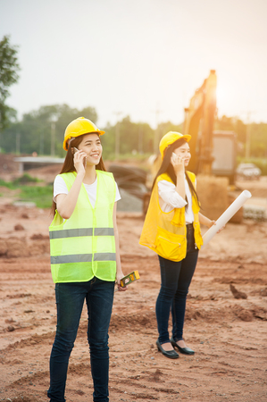 Two womens engineers using smart phone in a construction site