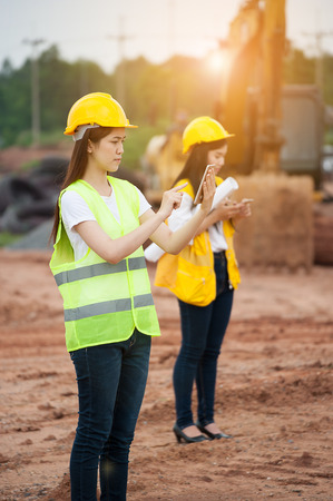 Two women engineers using smart phone in a construction site