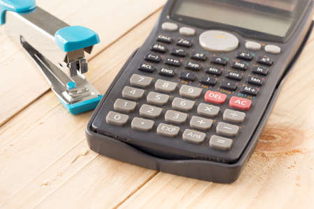 sceince: Old Calculator and Stapler on Wooden board Stock Photo