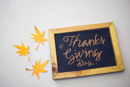 The word Thanksgiving written by hand on a blackboard in whitegrey background