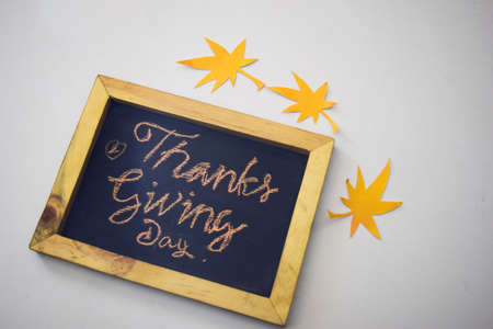 The word Thanksgiving written by hand on a blackboard in white/grey background Stock Photo