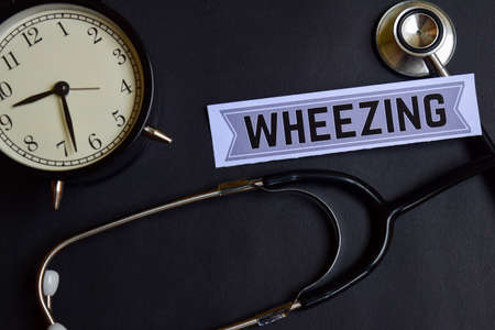 Wheezing on the paper with Healthcare Concept Inspiration. alarm clock, Black stethoscope. Stock Photo