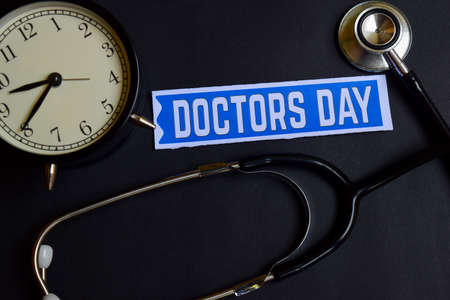 Doctors Day on the paper with Healthcare Concept Inspiration. alarm clock, Black stethoscope. Stock Photo